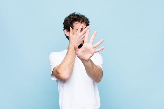顔を手で覆い、もう一方の手を前に出して止め、写真や写真を拒否する