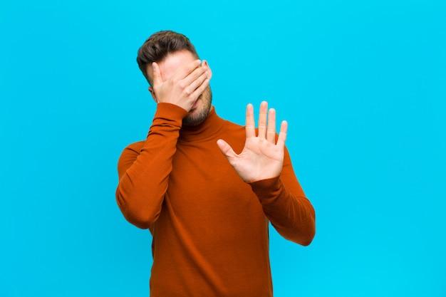 Закрыв лицо рукой и положив другую руку вперед, чтобы остановиться, отказываясь от фотографий или картинок