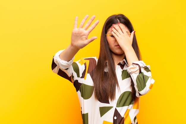 Covering face with hand and putting other hand up front, refusing photos or pictures