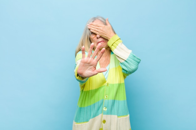 Covering face with hand and putting other hand up front to stop camera, refusing photos or pictures
