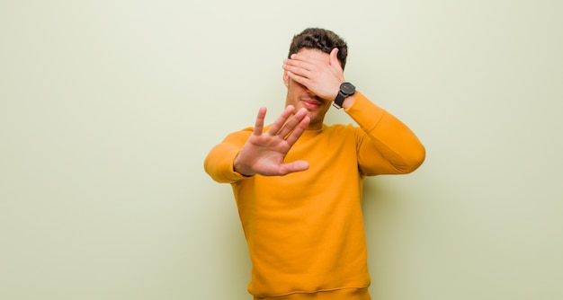 Covering face with hand and putting other hand up front to stop, refusing photos or pictures