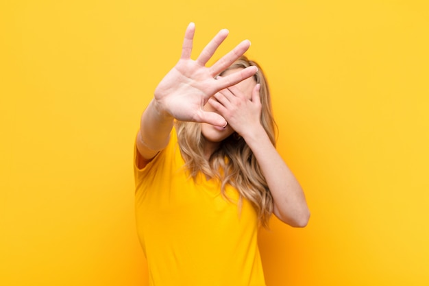 Covering face with hand and putting other hand up front to stop