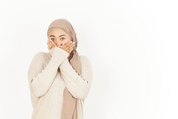 白い背景で隔離のヒジャーブを身に着けている美しいアジアの女性の口を覆う