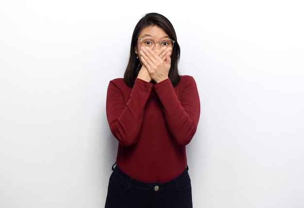 若い美しいアジアの女性の手で口を覆う白で隔離の赤いシャツを着る