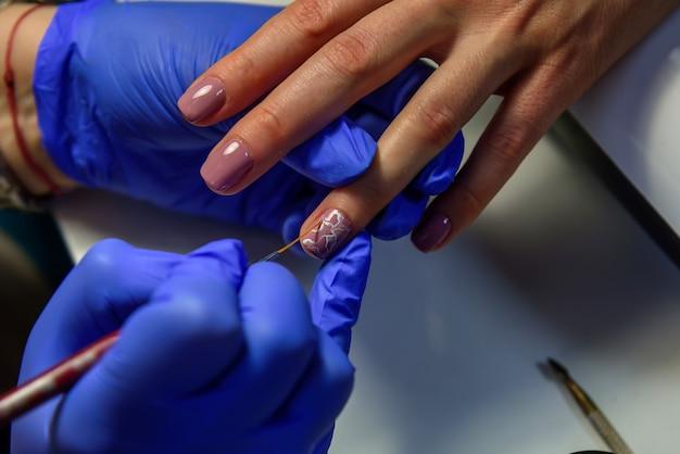 Покрытие ногтей гель-лаком, нанесение рисунка на ногтевую пластину. мастер маникюра в синих перчатках наносит лак тонкой кисточкой. маникюр в пастельных тонах.