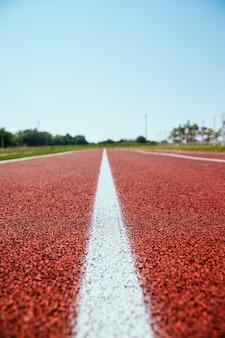 クローズアップでトレッドミルをカバーしています。スポーツフィールドに白い線でマークされています。スポーツをテーマにした背景と質感。