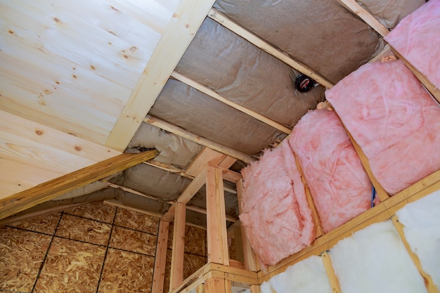 Covering view of layers of pink fiberglass insulation cold barrier