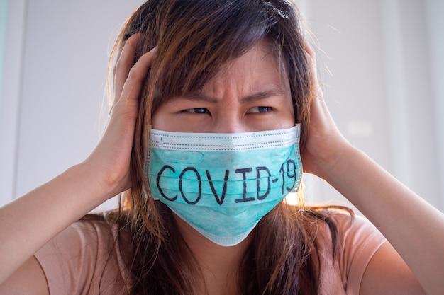 マスクされた女性がcovid-19を書くと、ウイルスや精神病の症状に感染する恐れがあります。 2019-ncovウイルス感染の状況は世界中に広がっています。保護するマスク
