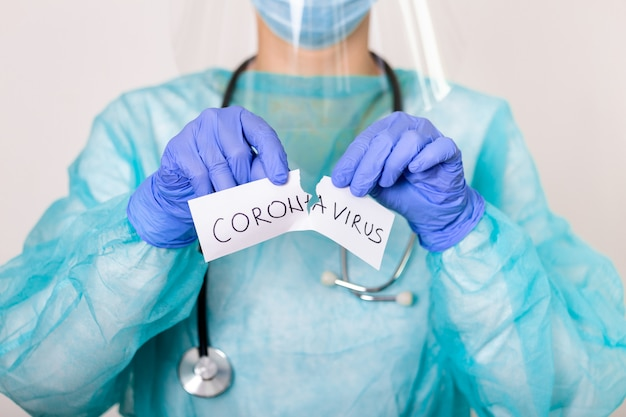 コロナウイルス検疫の概念。 covid-19.新規コロナウイルス(2019-ncov)。聴診器を持つ医師コロナウイルスという言葉で紙を引き裂きます。