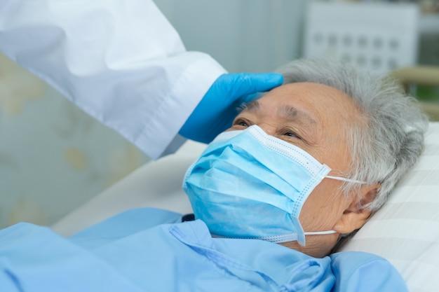 Доктор касаясь азиатскому старшему пациенту женщины нося лицевой щиток гермошлема в больнице для защищает новый вирус covid-19 коронавируса (2019-ncov).