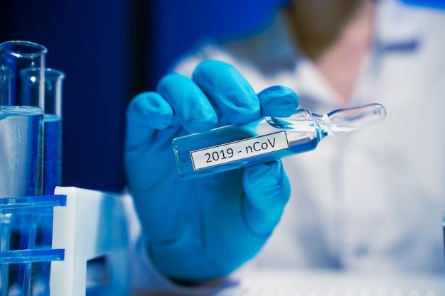 Covid-19(新型コロナウイルス感染症)(#文字数制限がない場合、初出時にかっこ書きを追加。 2019新しいコロナウイルス(2019-ncov)の概念。医師の手にワクチンが入ったアンプル。コロナウイルスに対するワクチン接種は、免疫力を強化するのに役立ちます。