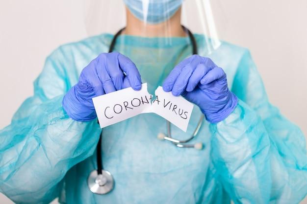 Понятие о коронавирусном карантине. covid - 19. новый коронавирус (2019-нков). врач со стетоскопом разорвите бумагу со словом коронавирус.