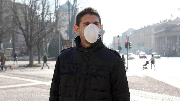 Covid-19病気のウイルスの拡散を防ぐフェイスマスクを身に着けている街の通りの男:コロナウイルス病2019。