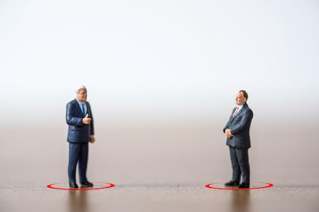 Covid-19コロナウイルスの蔓延を防ぐために社会的距離を保つことによって2人のビジネスマンマネージャーが立って話し合い、パンデミック感染を拡大します。社会的距離の概念。