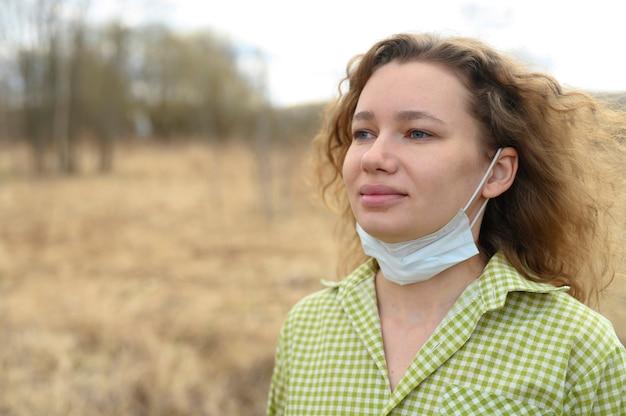 分離と検疫コロナウイルスcovid-19コンセプトを終了します。 30歳の若いヨーロッパの女性は彼女の顔から医療用マスクを取り外し、屋外の自然の中で新鮮な空気を吸い込みます