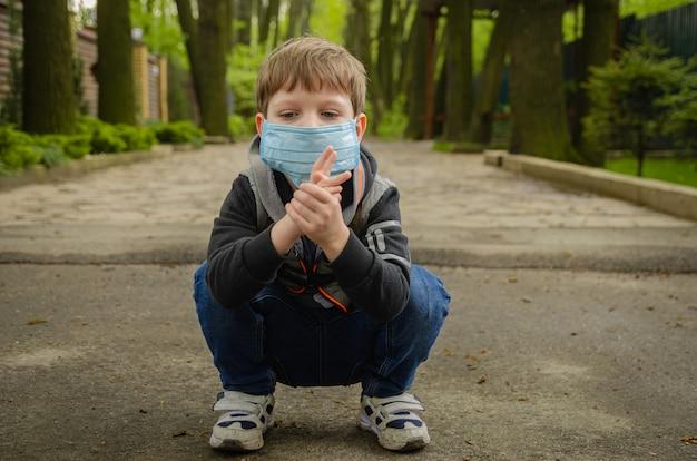 コロノウイルスのパンデミック(covid-19)のため、かわいい春の4歳の男の子が医療用マスクを着て公園を散歩します。