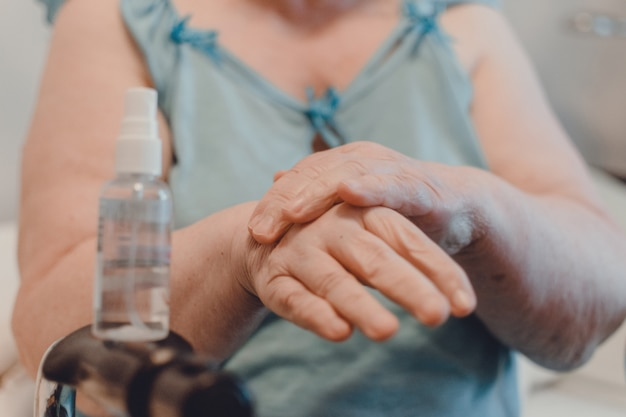 Профилактика коронавируса covid-19 для пожилых людей. старуха пользуется спиртосодержащим дезинфицирующим средством для рук с 60% спиртом, руки закрываются. как подготовиться к коронавирусу