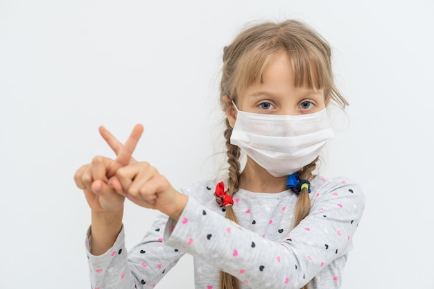 Covid-19 and air pollution pm2.5 concept. little girl wearing mask for protect pm2.5 and hands gesture for stop corona virus outbreak.