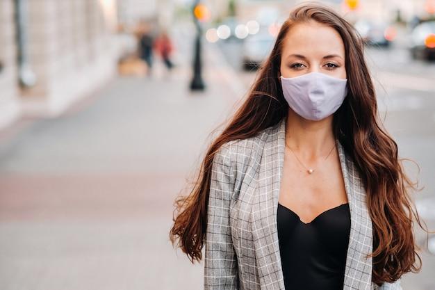Covid-19と大気汚染pm2.5の概念。パンデミック、路上で保護マスクを着用している若い女性の肖像画。健康と安全の概念。 Premium写真