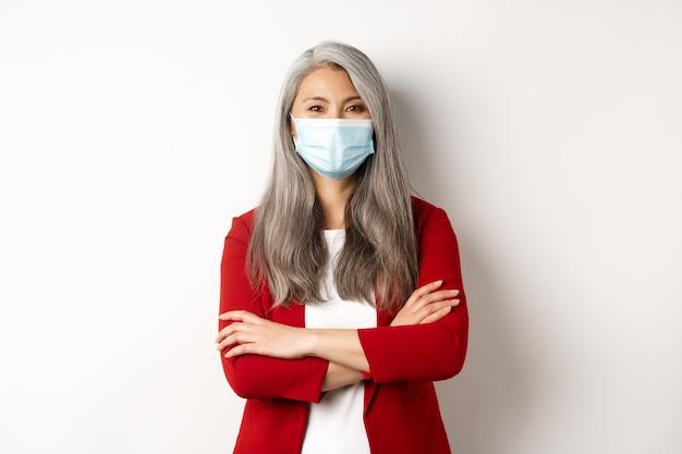 Covid-19 и концепция деловых людей. веселая азиатская дама в маске смотрит в камеру, скрестив руки на груди, как профессиональный, белый фон.