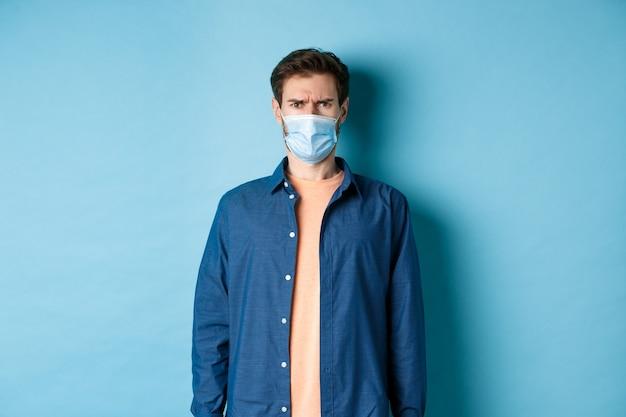 Covid-19 и концепция здравоохранения. разочарованный парень в медицинской маске хмурится, выглядит смущенным, стоя на синем фоне.