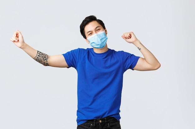 Covid-19とライフスタイルのコンセプト。のんきな幸せなアジア人男性、勝利のダンスで良いニュースを祝って、興奮して、良いニュースを聞いて、医療用マスクを着用