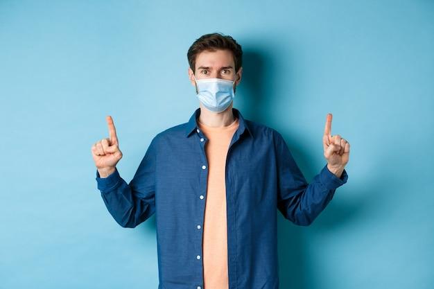 Covid-19 및 라이프 스타일 개념. 건강 하 고 행복 하 고, 빈 공간, 파란색 배경에서 손가락을 가리키는 얼굴 마스크에 잘 생긴 젊은 남자.