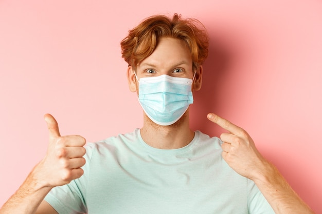 코비드-19와 전염병 개념. 잘생긴 빨간 머리 남자는 얼굴 마스크를 손가락으로 가리키고 코로나바이러스의 조치를 사용하여 엄지손가락을 위로 보여주며 분홍색 배경 위에 서 있습니다.