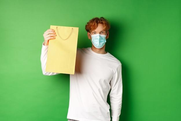 코비드-19와 전염병 개념. 쇼핑백을 보여주고 카메라를 보고 녹색 배경 위에 서 있는 얼굴 마스크를 쓴 놀란 남자.
