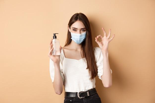 Covid-19 및 예방 조치 개념. 베이지 색 배경에 서 손 소독제 병 및 괜찮아 기호를 보여주는 얼굴 마스크에서 아름 다운 소녀.