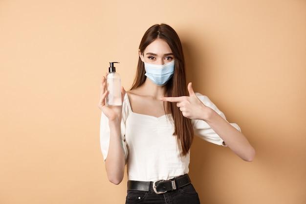 Covid-19 및 예방 조치 개념. 손 소독제의 병을 가리키는 의료 마스크에 웃는 소녀, 베이지 색 배경에 서있는 소독제를 보여주는.