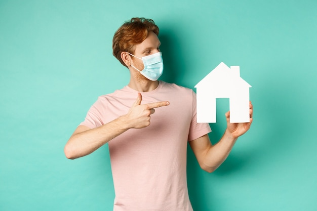코비드-19와 부동산 개념. 의료용 마스크를 쓴 빨간 머리 남자는 청록색 배경 위에 서 있는 종이 집 컷아웃을 가리키고 보고 있습니다.