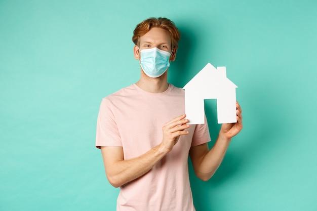 코비드-19와 부동산 개념. 얼굴 마스크를 쓴 행복한 청년은 종이 집 컷아웃과 미소를 보여주고, 민트 배경 위에 서서 부동산을 팔고 있습니다.
