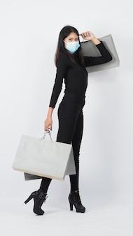 Covid19とショッピングコンセプト。フェイスマスクを身に着けているアジアの女性は買い物袋を保持します。少女と紙袋は、コロナウイルスの危機またはcovid19の発生時の買い物を表しています。買い物客とウイルスマスク。