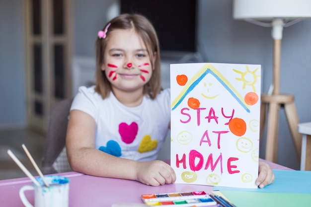 Covid -19하고 집 개념을 유지하십시오. 그녀의 얼굴에 휴가 또는 격리 witn 마우스 동안 집에서 혼자 그리기 작은 사랑 스럽다 귀여운 명랑 즐거운 소녀. 집에서 어린 시절 가정 활동, 아이들을위한 예술