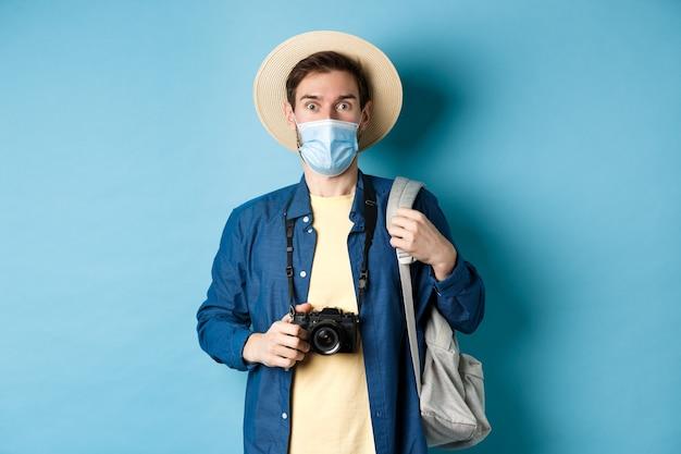 Covid-19と夏休みのコンセプト。麦わら帽子と医療マスクで興奮した観光客は畏敬の念を抱き、カメラを持って、パンデミック、青い背景の休日に写真を撮ります。