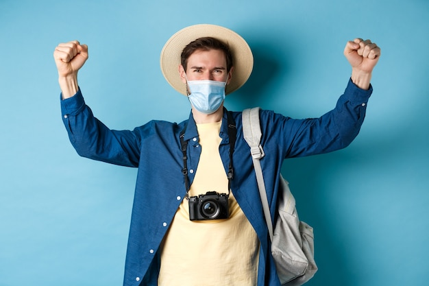 Covid-19と夏休みのコンセプト。休暇を祝って、フェイスマスクを着用し、喜びでイエスと叫び、手を上げて、青い背景の上に立って、幸せな笑顔の観光客。