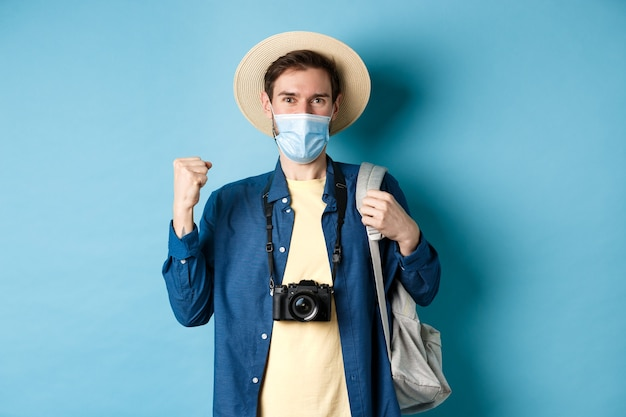 Covid-19と夏休みのコンセプト。医療マスクで海外旅行をしている幸せな若い男は、はいと言って、休暇、青い背景について陽気に、楽しく拳を上げます。