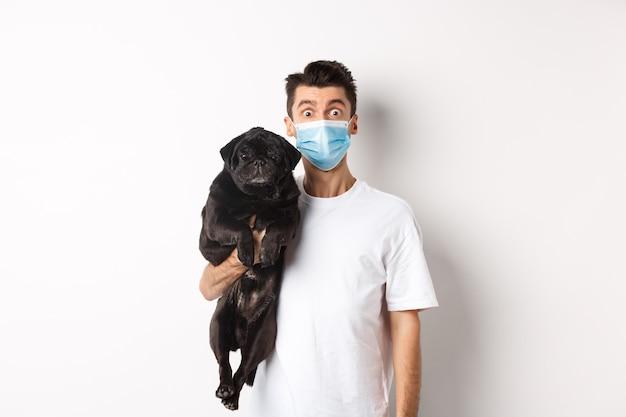 Covid-19, 동물 및 검역 개념. 흰색 위에 서있는 귀여운 검은 pug 개를 들고 의료 마스크에 재미 있은 젊은 남자