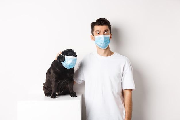 Covid-19、動物と検疫の概念。面白い若い男と医療マスクのパグ、カメラを見つめて、白い背景の上に立っている画像
