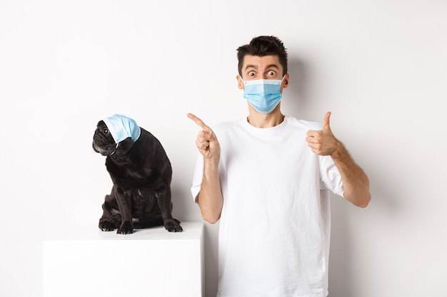 Covid-19、動物と検疫の概念。若い男と黒犬が医療用マスクを着用し、左上隅をパグで見て、所有者がプロモーションを称賛するために親指を立てています。