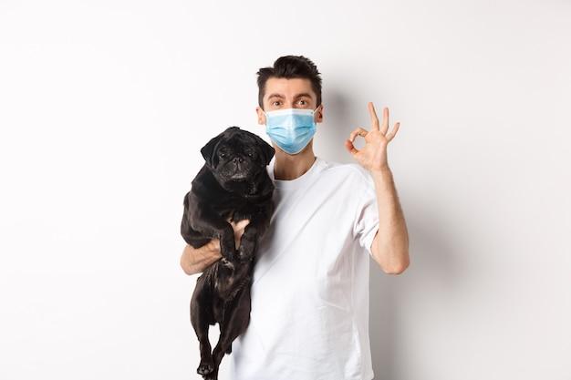 Covid-19, 동물 및 검역 개념. 귀여운 검은 퍼그 개를 들고 의료 마스크에 젊은 남자, 괜찮아 기호 표시, 좋아하고 승인, 흰색 위에 서