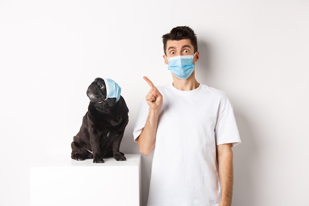 Covid-19, animals and quarantine concept. dog owner and cute black pug wearing medical masks, man pointing and puppy staring at upper left corner, white