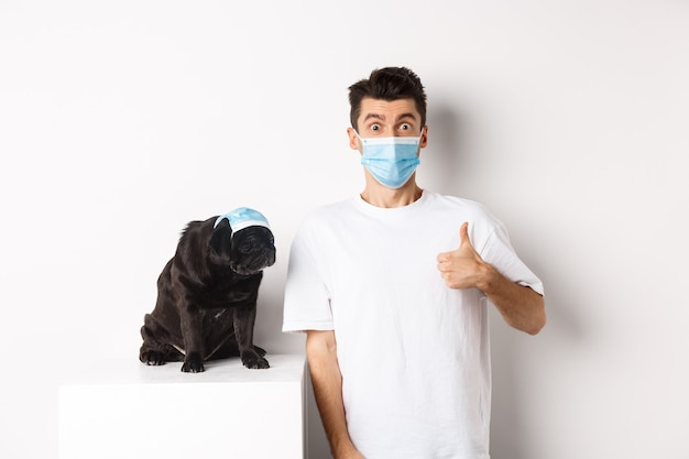 Covid-19, animals and quarantine concept. handsome young man and small dog wearing face masks, owner showing thumb up in approval, praise super cool product, white