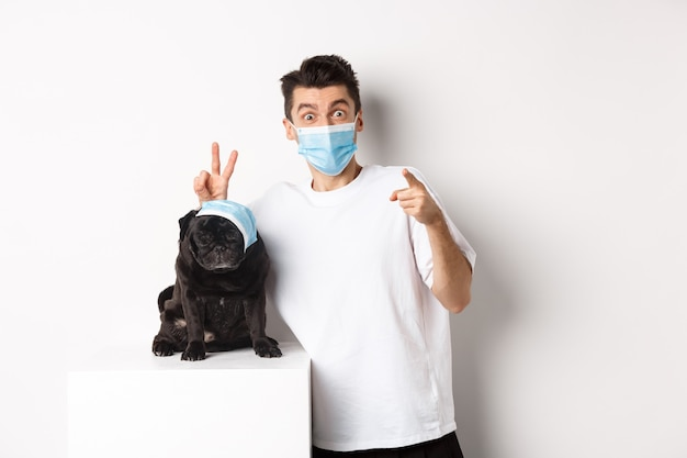 Covid-19, animals and quarantine concept. happy dog owner and cute pug wearing medical masks, man pointing finger at camera and making funny bunny ears on pet, white