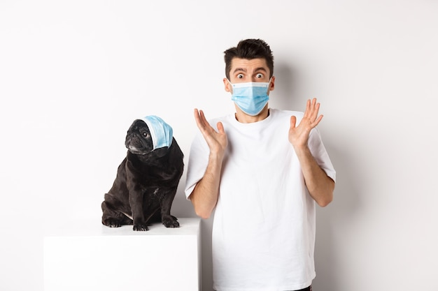 Covid-19, animals and quarantine concept. shocked dog owner and pug wearing medical masks, staring at camera amazed, standing over white