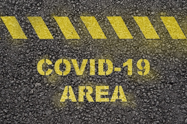 Covid-19 area text warning on the black asphalt road surface