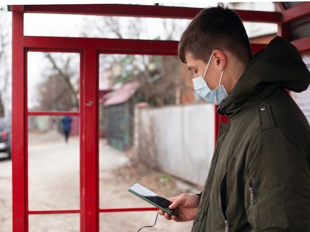 医療マスクの男はバス停に立っています。ウイルス性疾患covid-19麻疹インフルエンザ水chicken風邪を避けるために隔離されました。