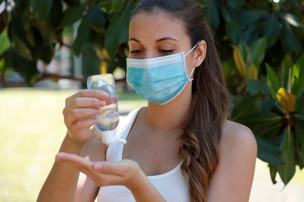 Covid-19 крупным планом спортивная женщина с хирургической маской, использующая дезинфицирующее средство со спиртовым гелем для рук в городском парке.