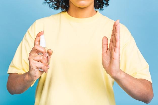 Covid-19 개념. 파란색 배경 위에 절연 손 소독제로 피부를 소독하는 흑인 흑인 여성. 코로나 바이러스 개념.